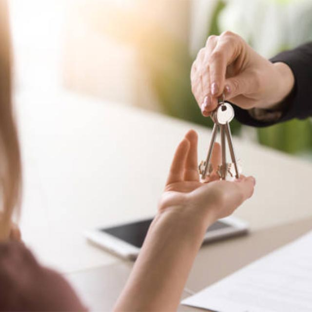 Man handing keys to woman